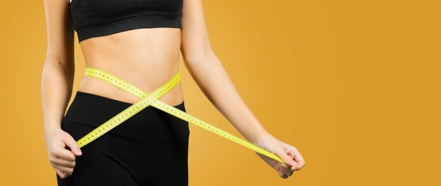 Jeune femme mesurant son tour de taille en tenue de sport